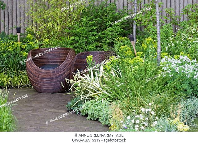 WOODEN CUP SEATS ON PAVED AREA. BAMBOO GRASSES EUPHORBIA GERANIUMS. WALKING BAREFOOT WITH BRADSTONE DES. SARAH EBERLE