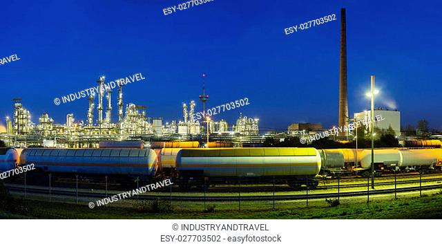 Panoramic view of a chemical plant and refinery with night blue sky and illumination, some freight trains in the foreground