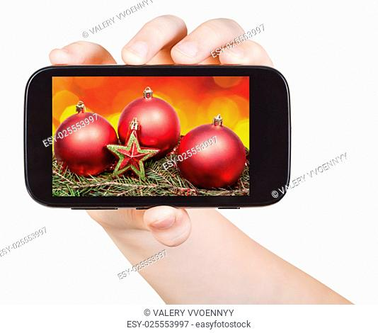 hand holds handphone with Christmas decorations on screen isolated on white background