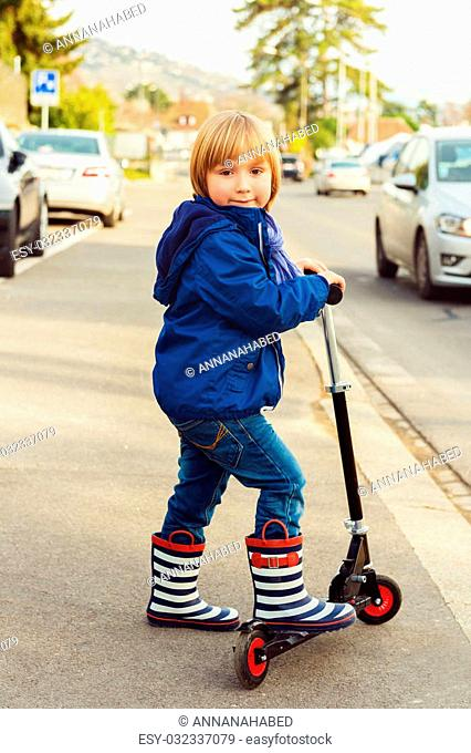 Little boy riding scooter in a city next to big road, wearing blue jacket and stripe rain boots