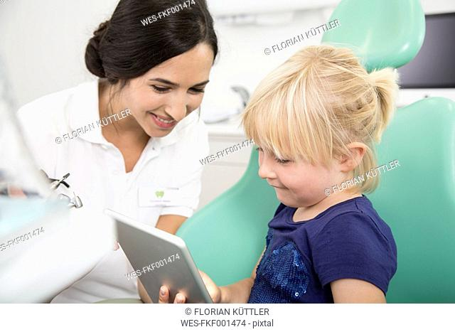 Dentist and smiling girl with digital tablet in dentist's chair