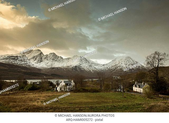 Clouds over isolated houses in front of snowcapped Cuillin mountain range, Scotland, UK