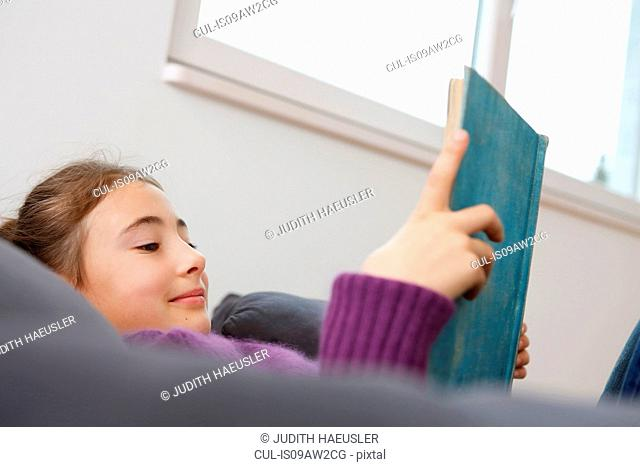 Low angle view of girl lying down reading book smiling