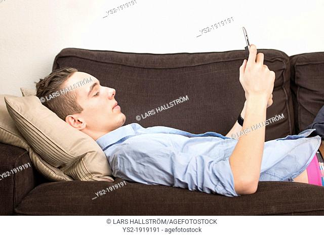 Lifestyle moment with a relaxed young adult male holding a digital tablet device in his hands
