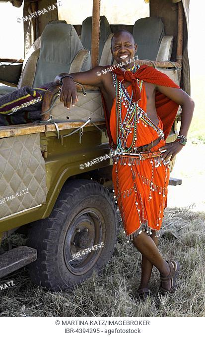 Maasai man, 28 years, in traditional shuka, leaning on safari vehicle, Mara Triangle, Masai Mara, Narok County, Kenya