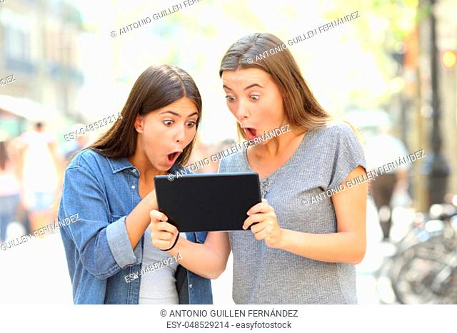 Two surprised friends finding online content in a tablet in the street