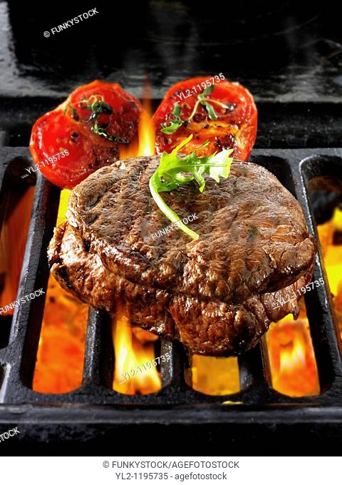 Beef fillet steaks & tomatoes being cooked on a bbq