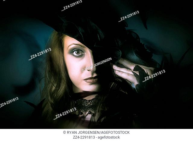Dark close-up photograph on the face of a beautiful mystical woman dancing in a soft haze of elegance. Black fashion concept