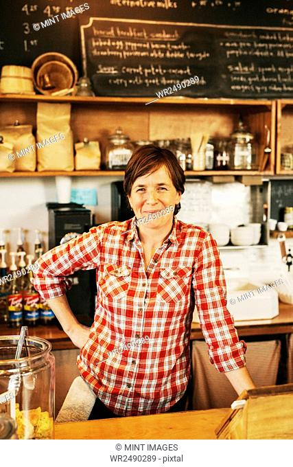 A woman in a coffee shop behind the counter, smiling, business owner