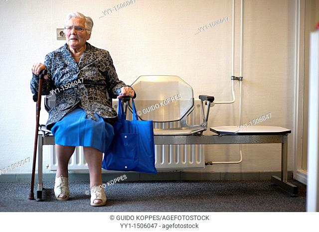 Rotterdam, Netherlands. A senior adult inhabitant of a Charlois nursing home waiting for his taxi, sitting in a seat near the exit doors of the building