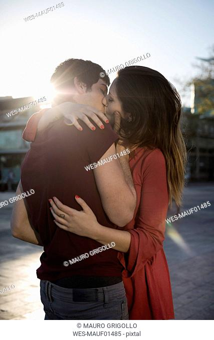 Affectionate young couple kissing on city square at sunset