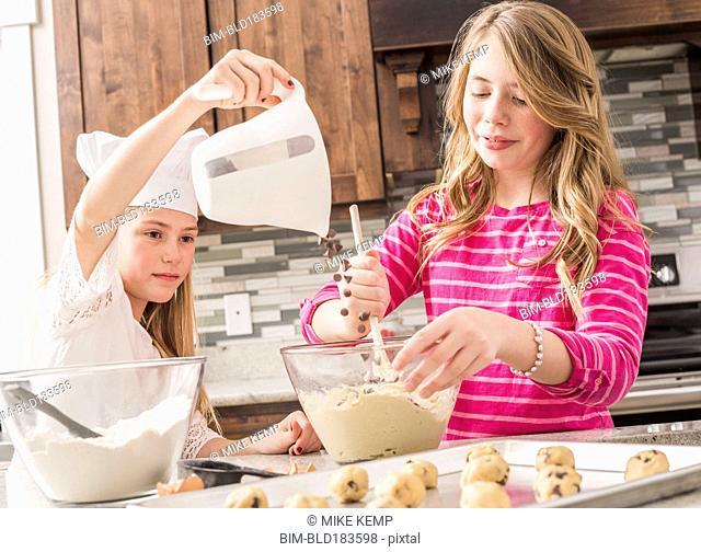 Caucasian girls baking in kitchen