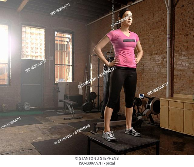 Young woman standing on table in gym