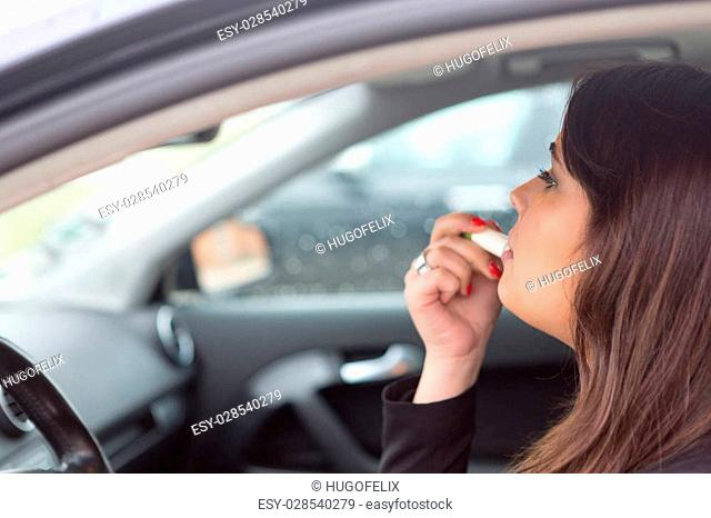 Business woman retouching her makeup while stopped in the traffic