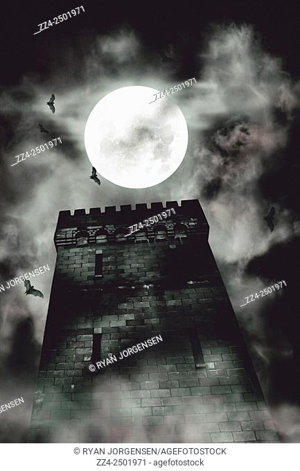 Spooky halloween style image of a creepy dark castle tower under a full moon of bats and atmospheric rising fog. Tower of terror