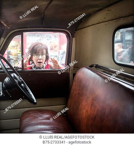 Woman looking through the window of a vintage car with surprised expression. London, England