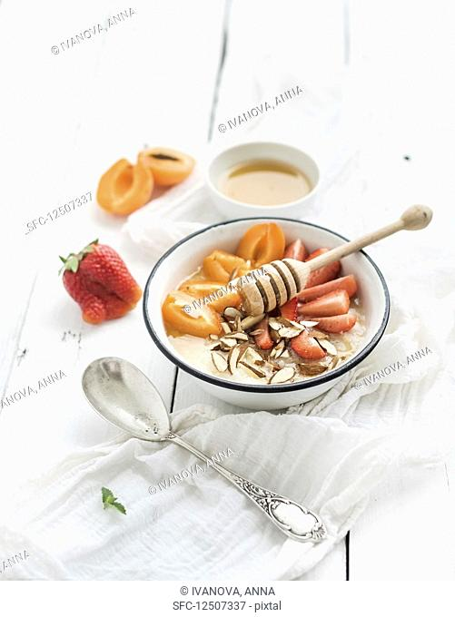 Healthy breakfast set. Rice cereal or porridge with fresh strawberry, apricots, almond and honey over white rustic wood backdrop