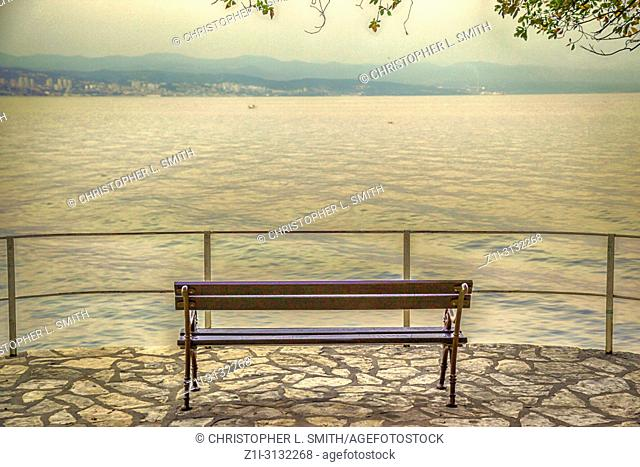 Empty bench seat overlooking the Adriatic coastline of Criatia at sunset from Opatija