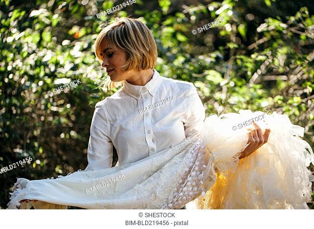 Bride holding wedding gown in garden