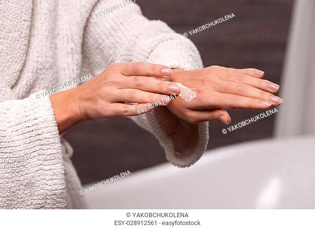 Close up of arm of young woman applying cream on her hand