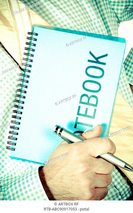 Mid section view of a man holding a spiral notepad and a ballpoint pen