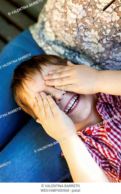 Little boy lying on mother's lap covering eyes with his hands