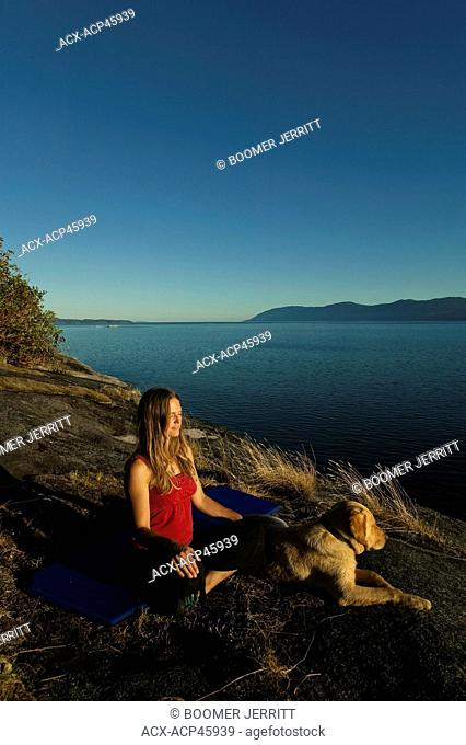 A young women meditates alongside her dog to a setting sun at Stillwater Bluffs, a popular recreation area south of Powell river on the Sunshine coast