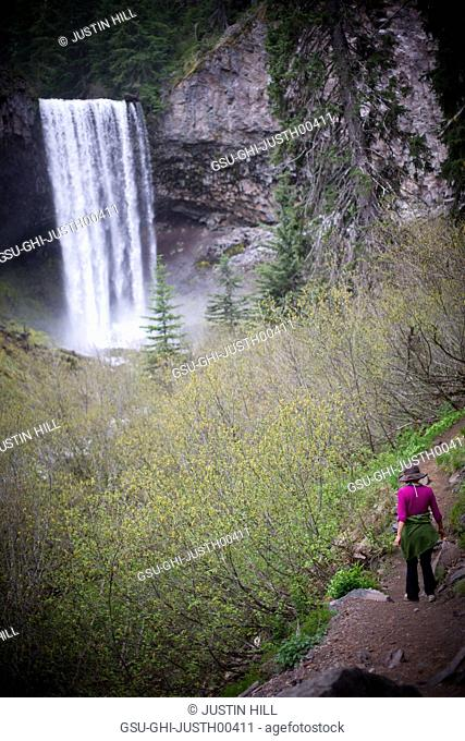 Woman Hiking on Rural Path with Waterfall in Background