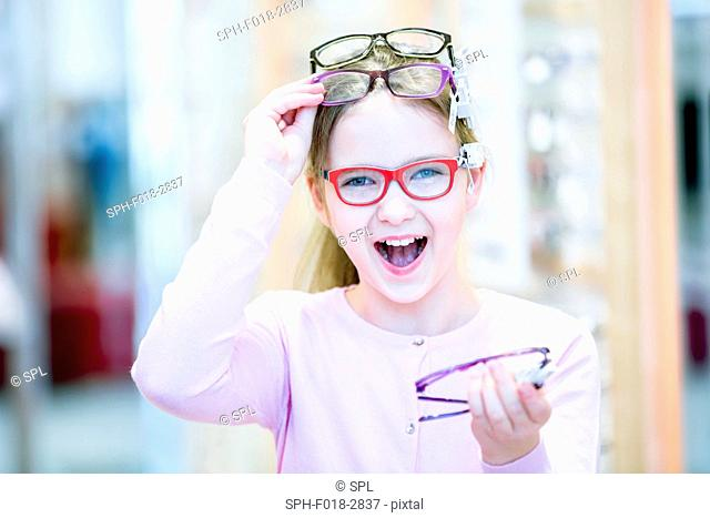 Portrait of girl trying glasses in optometrist's shop