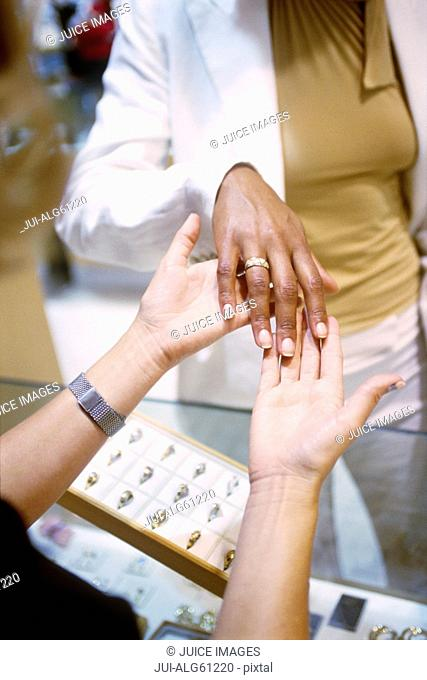 Young woman trying on rings at the jewellery store