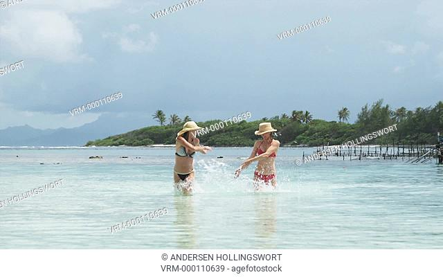 two women splashing in the ocean