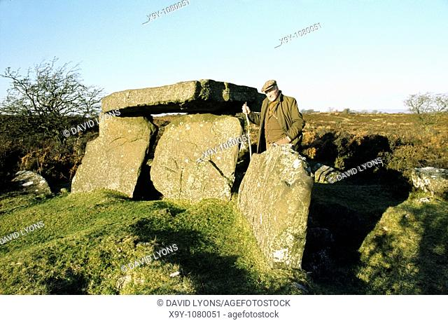 Old man beside prehistoric Neolithic burial chamber dolmen known as Craig's Tomb near Ballymoney, Co Antrim, Northern Ireland
