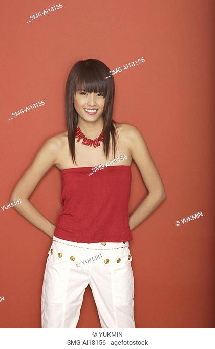Young woman in red tube top standing against red wall