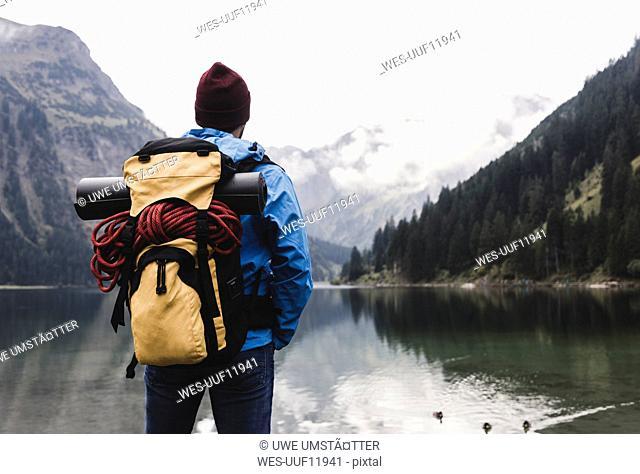 Austria, Tyrol, Alps, hiker standing at mountain lake