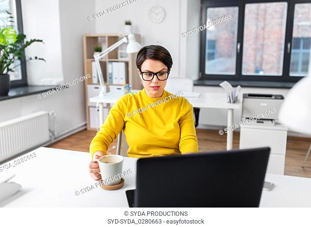 businesswoman with laptop drinks coffee at office