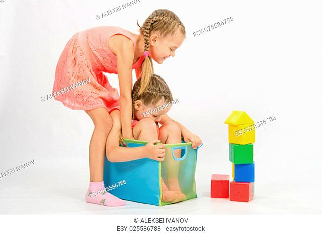 The four-year and six-year old girl playing in a European-style cubes, isolated on a light background
