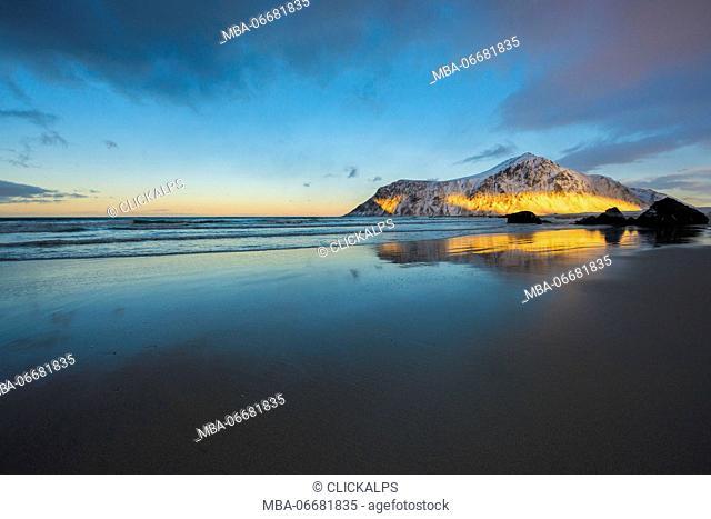 Aray of light hits a mountain reflected in the water, Skagsanden beach, Lofoten islands, Norway