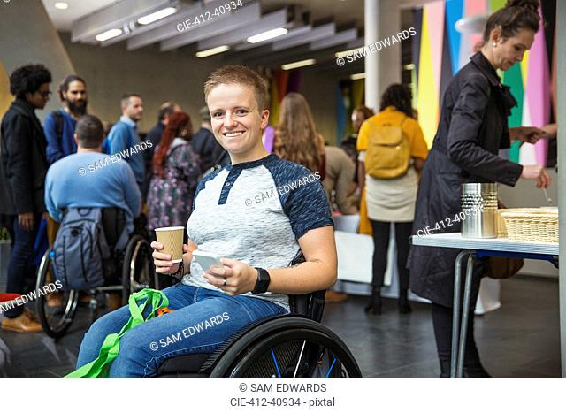 Portrait smiling, confident woman in wheelchair using smart phone at conference