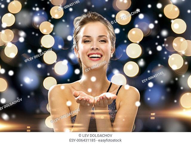 people, holidays, advertisement, christmas and luxury concept - laughing woman in evening dress holding something imaginary over night lights and snow...