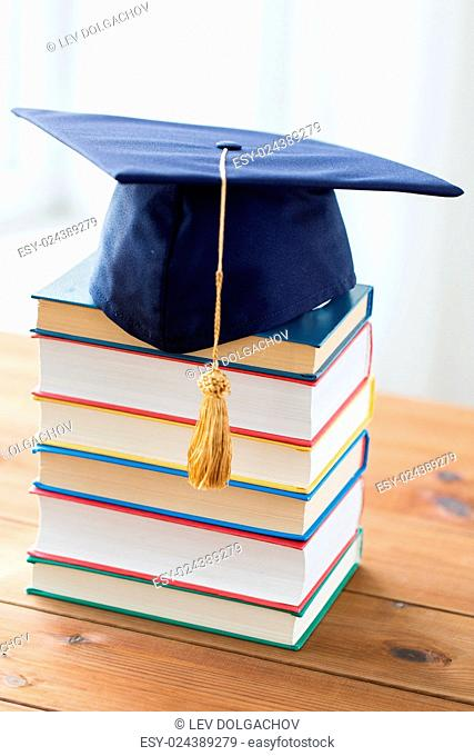 education, school, graduation and knowledge concept - close up of books and mortarboard on wooden table