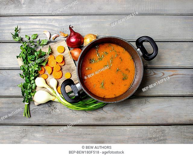 Top view on pot of tomato soup and fresh vegetables on old wooden table