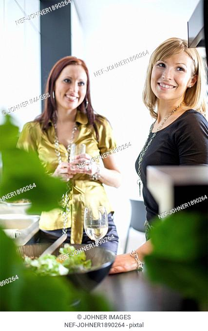 Two smiling women looking away