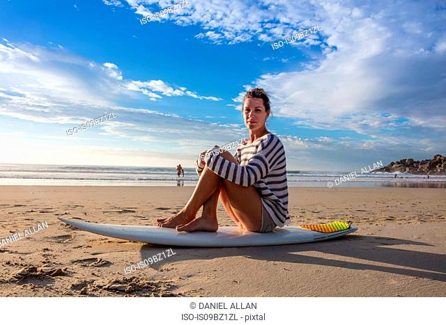 Female surfer sitting on surfboard at beach, portrait, Cape Town, Western Cape, South Africa