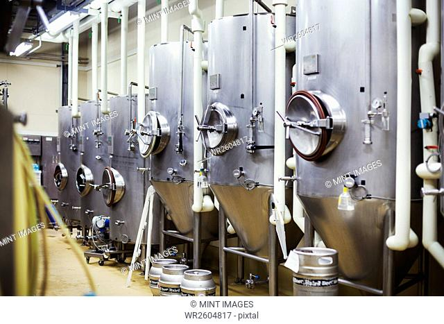 Row of large metal beer tanks in a brewery