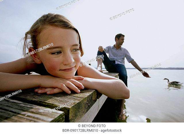 portrait of young girl on pier with father sitting in background