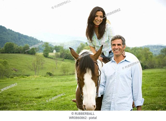 woman sitting on a horse with a man beside her
