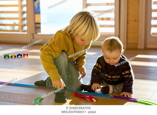 Little boy and his brother playing with toy train on the wooden floor at home