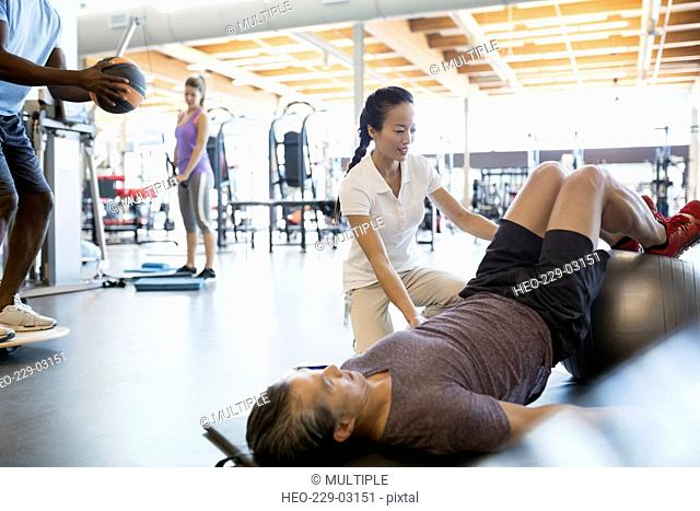 Physical therapist guiding patient fitness ball bridge pose