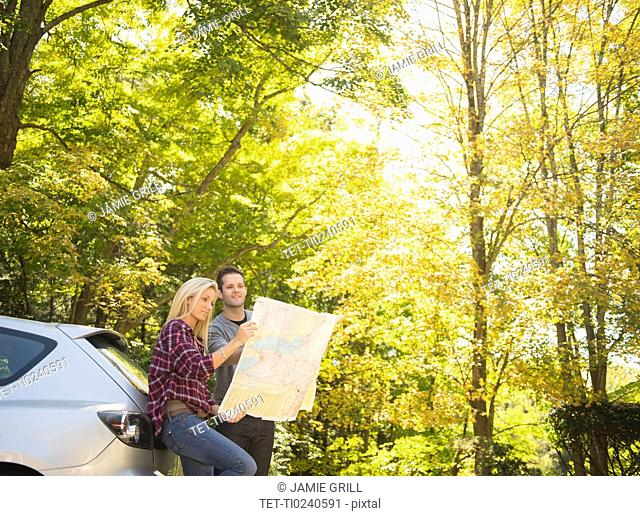 Couple leaning against car and reading map