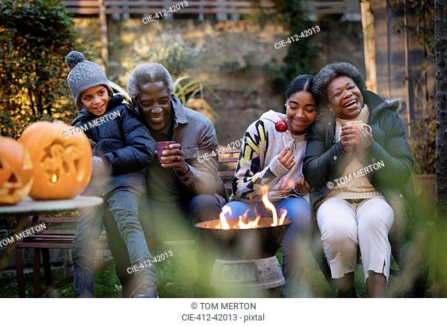 Grandparents and grandchildren enjoying autumn backyard campfire